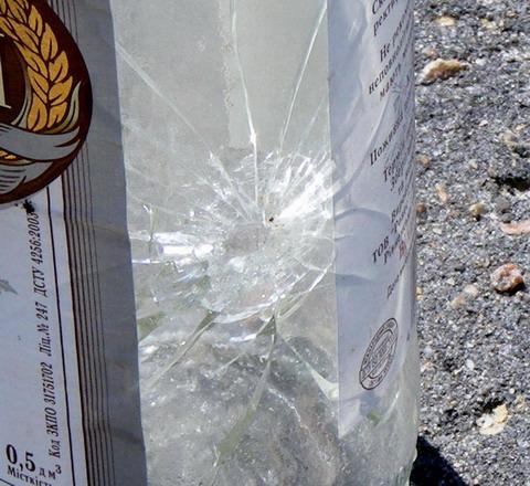 Пистолет Аникс. Входное отверстие пули в стеклянной бутылке.