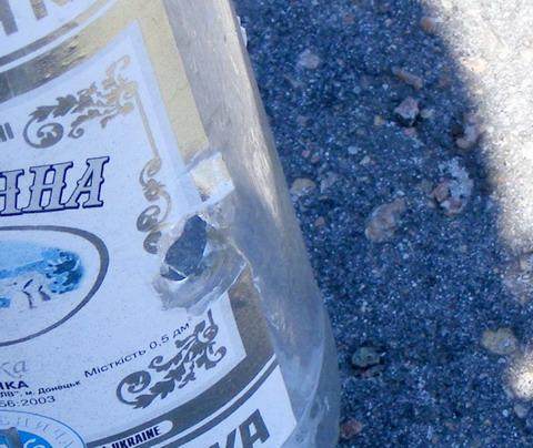 Пистолет Аникс. Выходное отверстие пули в стеклянной бутылке.