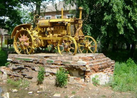 """Лугины. Трактор возле бывших мастерских """"Сельхозтехники""""."""